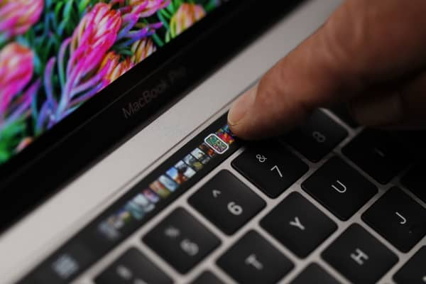 An Apple employee points to the Touch Bar on a new Apple MacBook Pro laptop