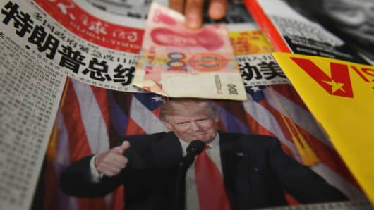 A vendor picks up a 100-yuan note above a newspaper featuring a photo of U.S. President-elect Donald Trump, at a newsstand in Beijing on November 10, 2016.