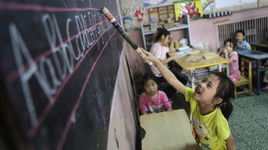 A girl recites English letters for other students during class at a kindergarten for children of migrant workers, in Beijing.