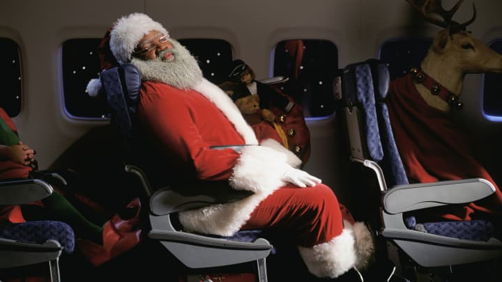 Santa clause sleeping in an airplane seat