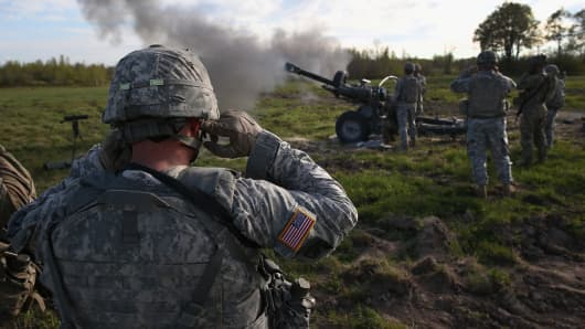 The 10th Mountain Division soldiers plug their ears while comrades fire a 105mm Howitzer during a training mission for future conflicts on May 18, 2016 at Fort Drum, New York.