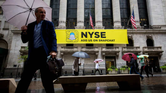 Pedestrians hold umbrellas while walking past a Snapchat sign displayed outside of the New York Stock Exchange.