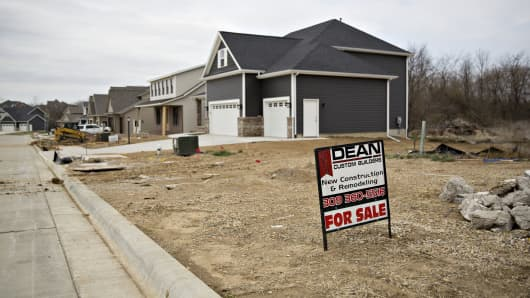 A 'For Sale' sign stands in a vacant lot near new homes in Dunlap, Illinois.