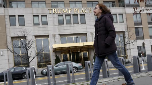 A woman walks past a Trump Place building, part of an apartment complex on the Upper West Side of Manhattan, in New York.