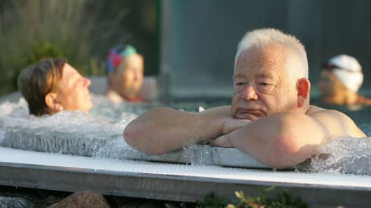 An elderly man sits in a public swimming pool