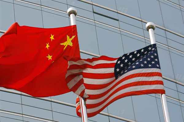 US and a Chinese flag wave outside a commercial building