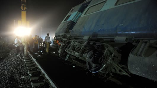 Rescue workers operate at the site of a derailed train near Pukhrayan in Kanpur district on November 20, 2016.