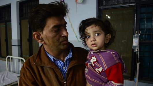 A 40-year-old man holds his daughter in a district hospital after the derailment of an Indore-Patna Express train on Sunday morning.