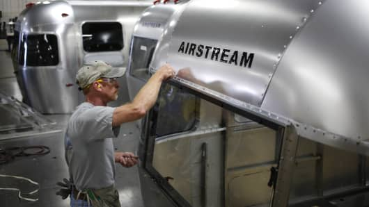 A factory worker installs rivets on the rear window of an Airstream RV travel trailer at the company's assembly plant in Jackson Center, Ohio.