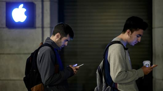 Customers check their mobile phones as they wait in line for their Iphone 7 and 7 Plus on September 16, 2016 in Madrid, Spain.