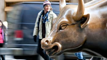 A pedestrian passes the bull statue in the Financial District near the New York Stock Exchange in New York.