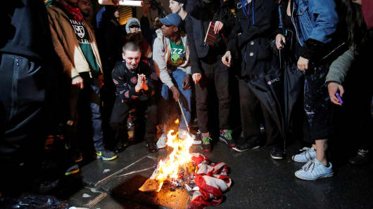 Protesters burn a U.S. flag outside Trump Tower following President-elect Donald Trump's election victory in New York, November 9, 2016.