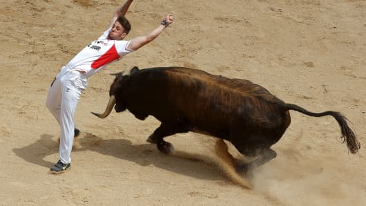 A 'recortador' dodges a bull at the San Fermin Running of the Bulls festival in Pamplona, Spain.