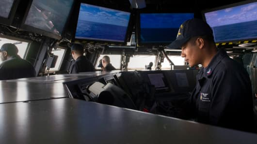Officer stands watch on bridge of USS Zumwalt. The new warship requires roughly half the crew size of older destroyers.
