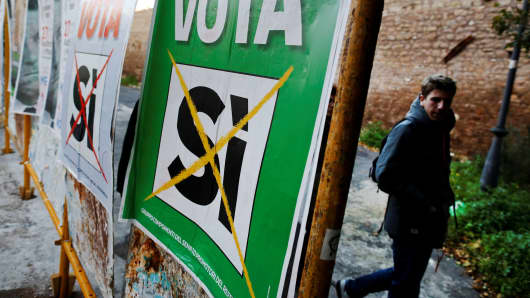 A man walks next to a poster in support of the 'Yes' vote in the upcoming constitutional reform referendum in Rome, Italy November 30, 2016.