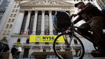 A man rides a bicycle past the New York Stock Exchange in New York.
