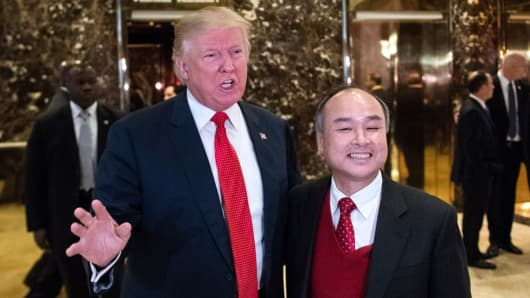 President-elect Donald Trump walks out with SoftBank's Masayoshi Son to speak to media in the lobby at Trump Tower in New York, Tuesday, Dec. 6, 2016.