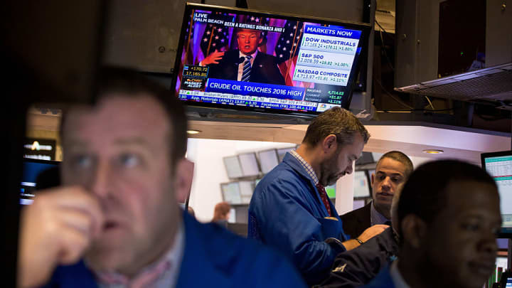 Donald Trump is seen speaking on a monitor as traders work on the floor of the New York Stock Exchange (NYSE) in New York, U.S.