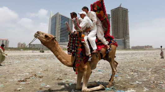 Men sit on a camel as they prepare to take a ride along Clifton beach in Karachi, Pakistan.