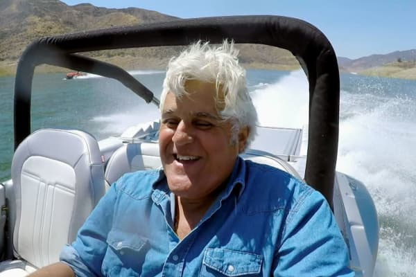 Jay Leno is all smiles as he tears across the water in … a car.