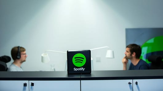 A Spotify Ltd. logo sits on display as employees work at desktop computers inside the music streaming company's offices in Berlin, Germany, on Friday, June 17, 2016.