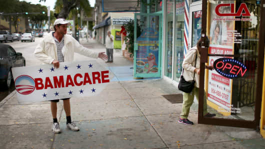 Pedro Rojas holds a sign directing people to an insurance company where they can sign up for the Affordable Care Act.