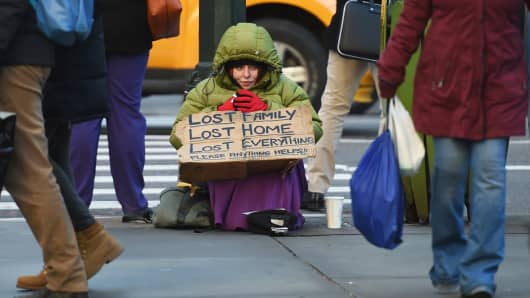 A homeless woman sits on 5th Avenue at 42nd Street in New York as she tries to stay warm in the cold temperatures.