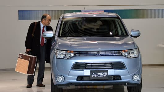 A customer looks at Mitsubishi Motors' new plug-in hybrid SUV 'Outlander PHEV' at the company's showroom in Tokyo on February 5, 2013.