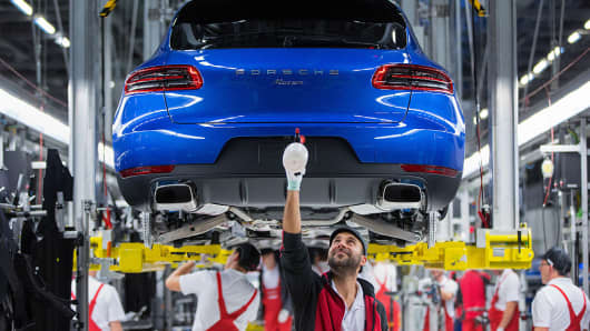 Employees work on the Porsche Macan sports utility vehicle assembly line inside the Porsche Leipzig GmbH factory, a unit of Porsche AG, in Leipzig, Germany, on Thursday, Dec. 1, 2016.