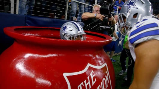 Ezekiel Elliott #21 of the Dallas Cowboys celebrates after scoring a touchdown by jumping into a Salvation Army red kettle during the second quarter against the Tampa Bay Buccaneers at AT&T Stadium on December 18, 2016 in Arlington, Texas.
