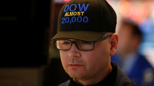 "Specialist trader Mario Picone wears a ""DOW Almost 20,000"" cap as he works at his post on the floor of the New York Stock Exchange (NYSE) in New York City, U.S., December 15, 2016."