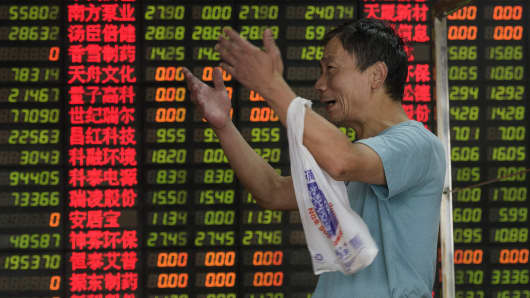 An investor reacts in front of screens showing stock market movements at a brokerage house in Shanghai.
