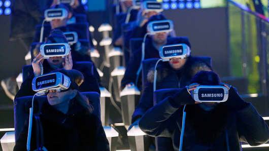 Visitors play a game with the virtual reality head-mounted Samsung Gear VR powered by Oculus at Le Grand Palais on December 15, 2016 in Paris, France.