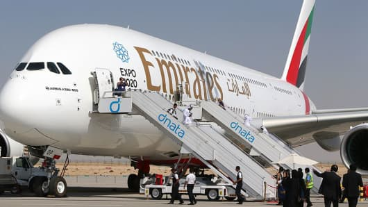 Visitors look at an Emirates airline's Airbus A380 dislayed at the Dubai Airshow on November 9, 2015.