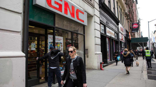 People walk past a GNC store in New York City.