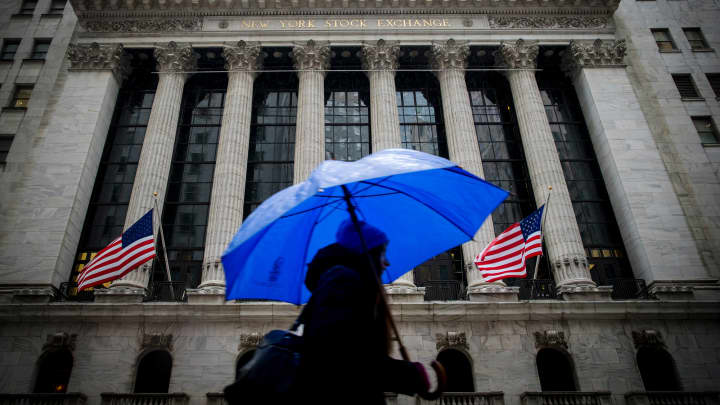 A pedestrian carries an umbrella as she passes by the New York Stock Exchange.