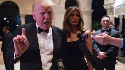 President-elect Donald Trump answers questions from reporters accompanied by wife Melania for a New Year's Eve party December 31, 2016 at Mar-a-Lago in Palm Beach, Florida.