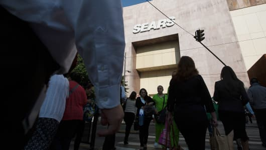 Pedestrians walking past a Sears store.