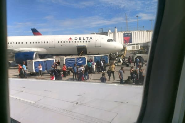 "A passenger photo of travelers disembarking when the shooting began at Fort Lauderdale-Hollywood International Airport. Passenger commented """"We are safe. Plane had just landed and about half of plane had gotten off. We're at back of plane. Suddenly an announcement came over speaker for everyone to get back on plane and take seats."""