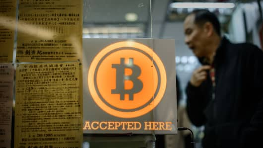 A man walks out of a shop displaying a bitcoin sign during the opening ceremony of the first bitcoin retail shop in Hong Kong on February 28, 2014.