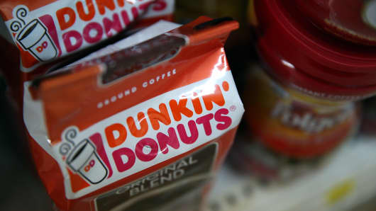 Packages Dunkin' Donuts and Folgers coffee are displayed on a shelf at a grocery store.