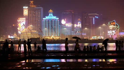 People walk on a water front near a strip of casinos in Macau.