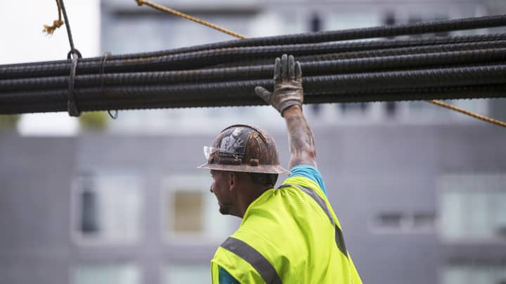 A contractor moves steel rebar while working on the construction site in New York.