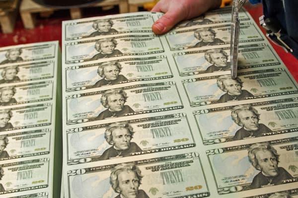 A pressman picks up a stack of uncut sheets of USD 20 bills at the US Bureau of Engraving in Washington, DC.