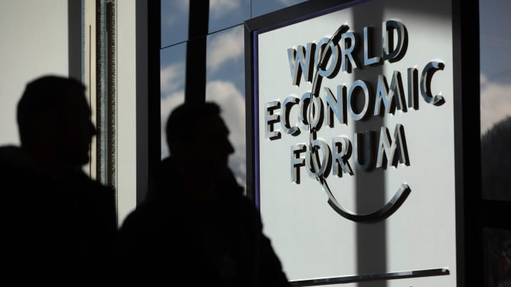 Visitors walk past a WEF sign outside the Congress Center ahead of the World Economic Forum (WEF) in Davos, Switzerland, on Monday, Jan. 16, 2017.