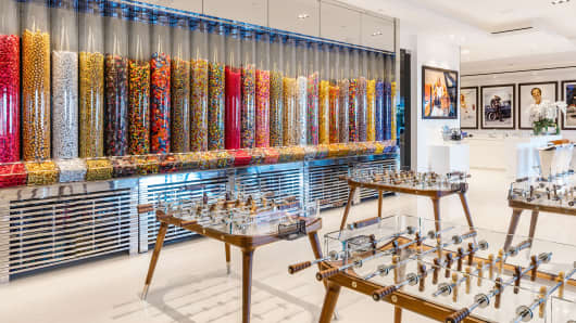 A giant candy wall borders an entertainment area that features four glass foosball tables and a custom-built glass ping pong table.