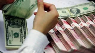 A bank teller counts the stack of Chinese yuan and US dollars at a bank in Shanghai.