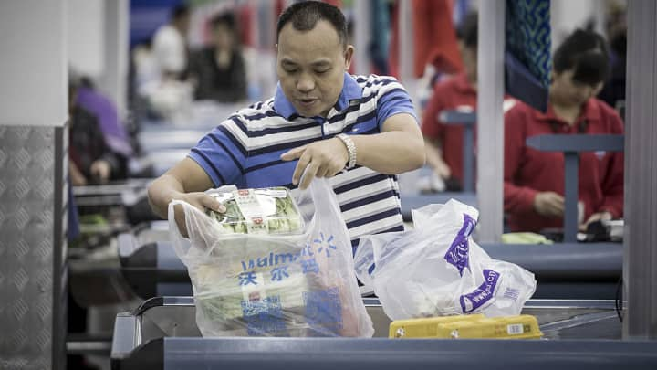 A customer arranges a shopping bag at a check-out counter inside a Wal-Mart Stores Inc.'s Sam's Club store in Shenzhen, China, on Tuesday, Oct. 18, 2016.