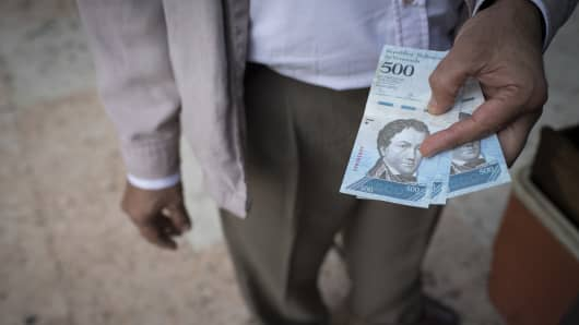 A man holds a 500 Bolivar banknotes in Caracas, Venezuela