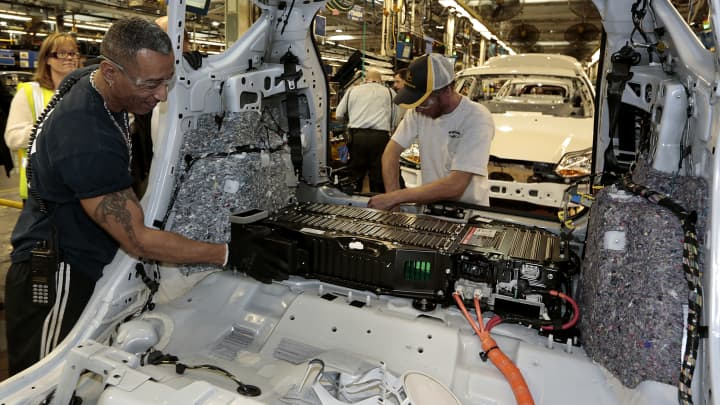 Employees install electric batteries on a Ford Motor Co. C-MAX Energi plug-in hybrid vehicle on the production line at the company's assembly plant in Wayne, Michigan.